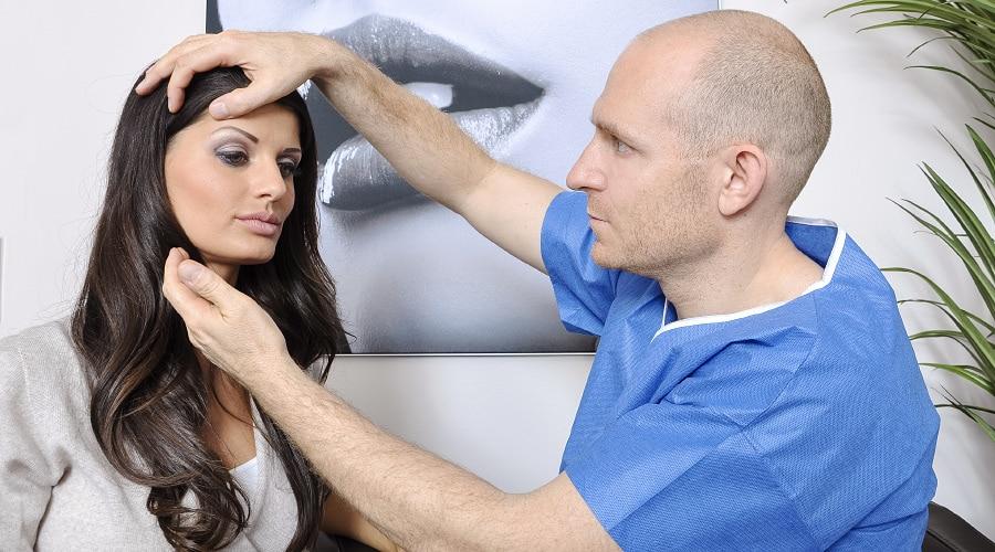 Plastischer Chirurg hebt in der Beratung Augenbraue der Patientin an.