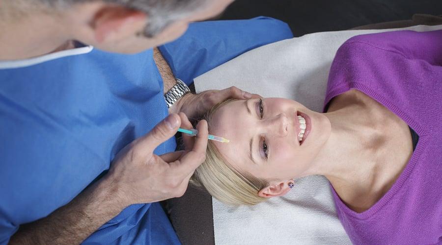 Plastischer Chirurg führt eine Faltenunterspritzung bei Patientin durch
