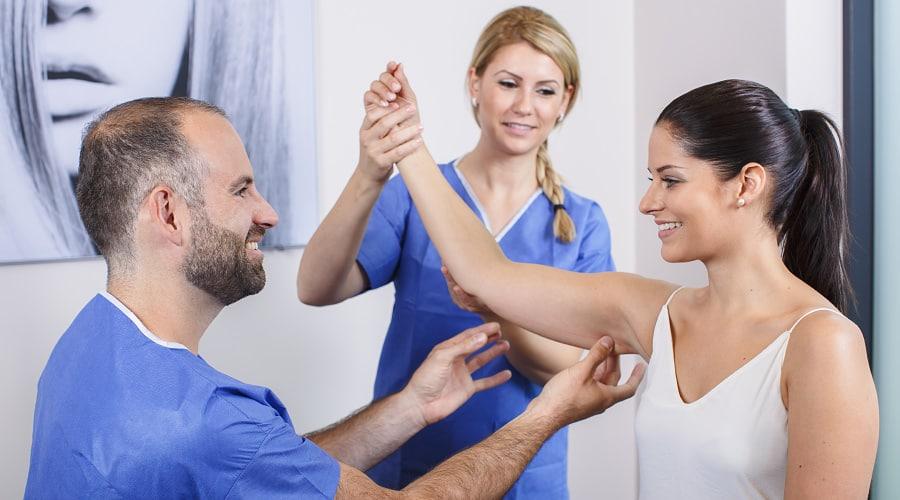 Arzt berät Patientin über Oberarmstraffung