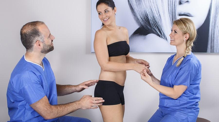Medizinisches Personal beurteilt bei Patientin, ob eine Po-Vergrößerung möglich ist.