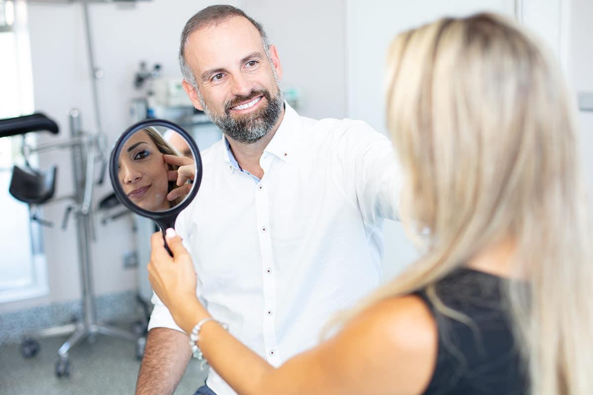 Schönheitschirurg mit Patientin während der Beratung für eine Unterlidstraffung